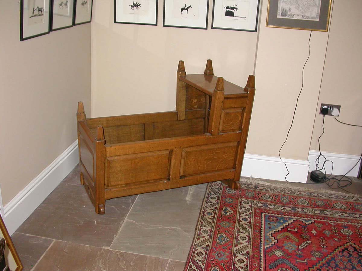 Oak baby rocking cradle with raised panels and head nest, with bevelled finials on all top corners
