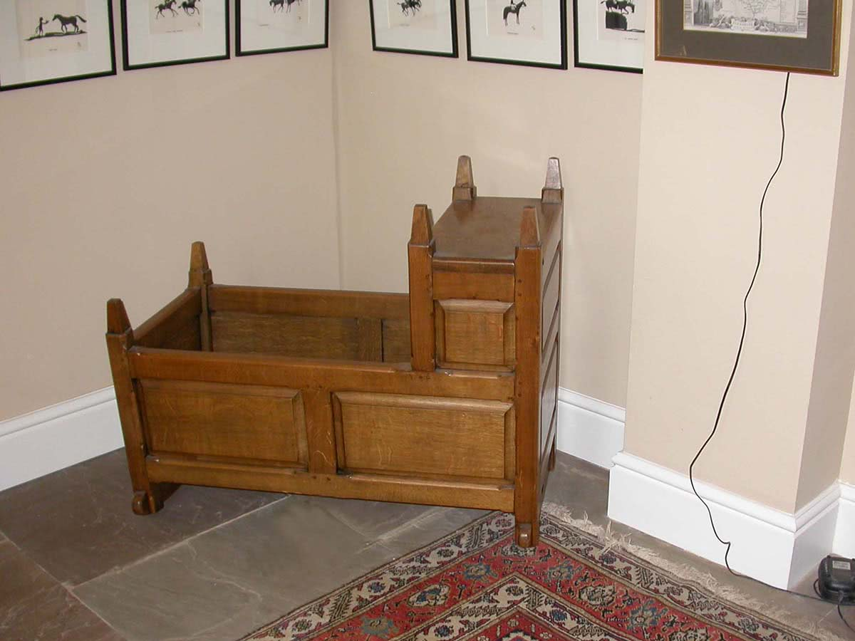Old fashioned oak baby rocking cradle with raised panels and head nest