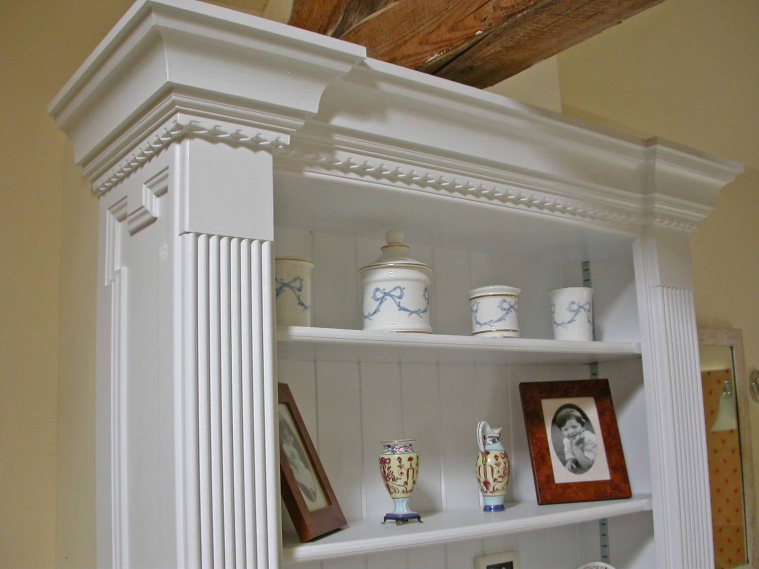 Close up of reeded columns and moulded cornice on fitted bathroom cabinets