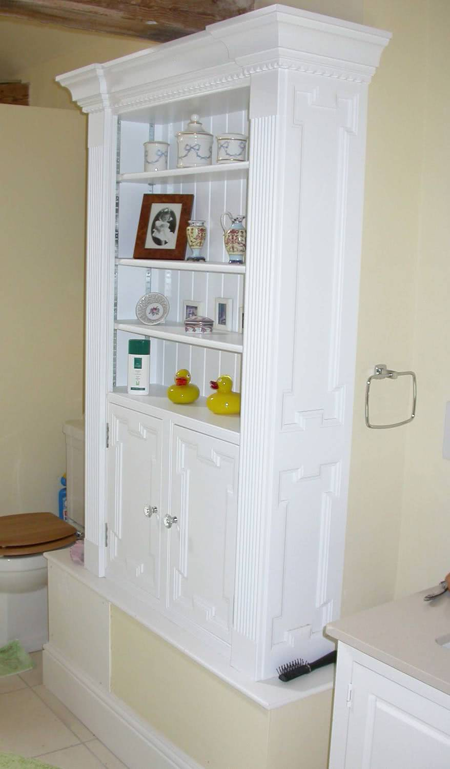 Side angle of fitted bathroom cabinets with open shelves painted MDF