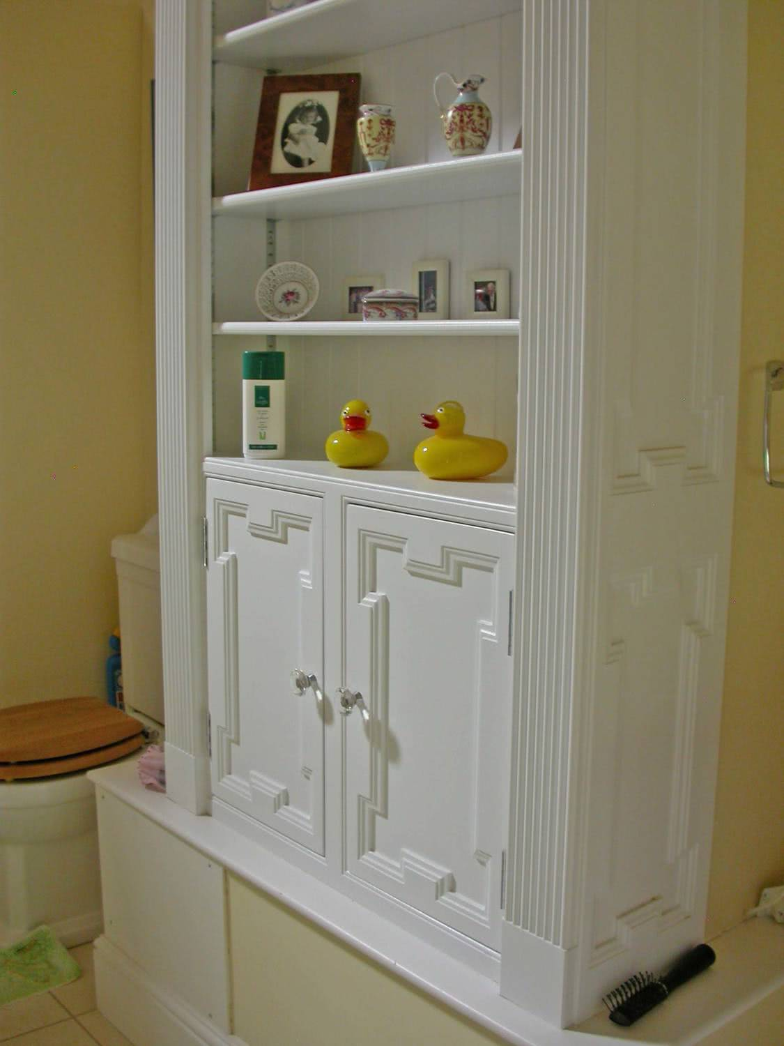 Lower section of fitted bathroom cabinets with open shelves. Moulded insert panels on each door with transparent door handles