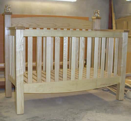 Front on angle of handmade baby cot, showing the delicate curving bottom and top lines