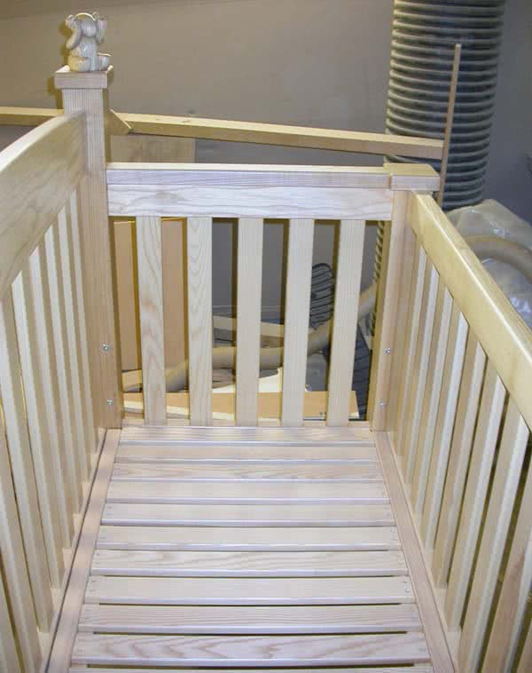 Shallow angled shot peering over the side of baby cot showing the depth and bottom of large babies cot