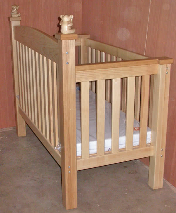 Rear view angled at 45 degrees to the corner of a handmade baby cot complete with new mattress