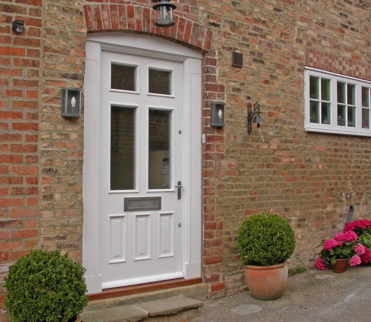 Exterior view of bespoke fitted meranti hardwood door with four double glazed windows and with three raised panels