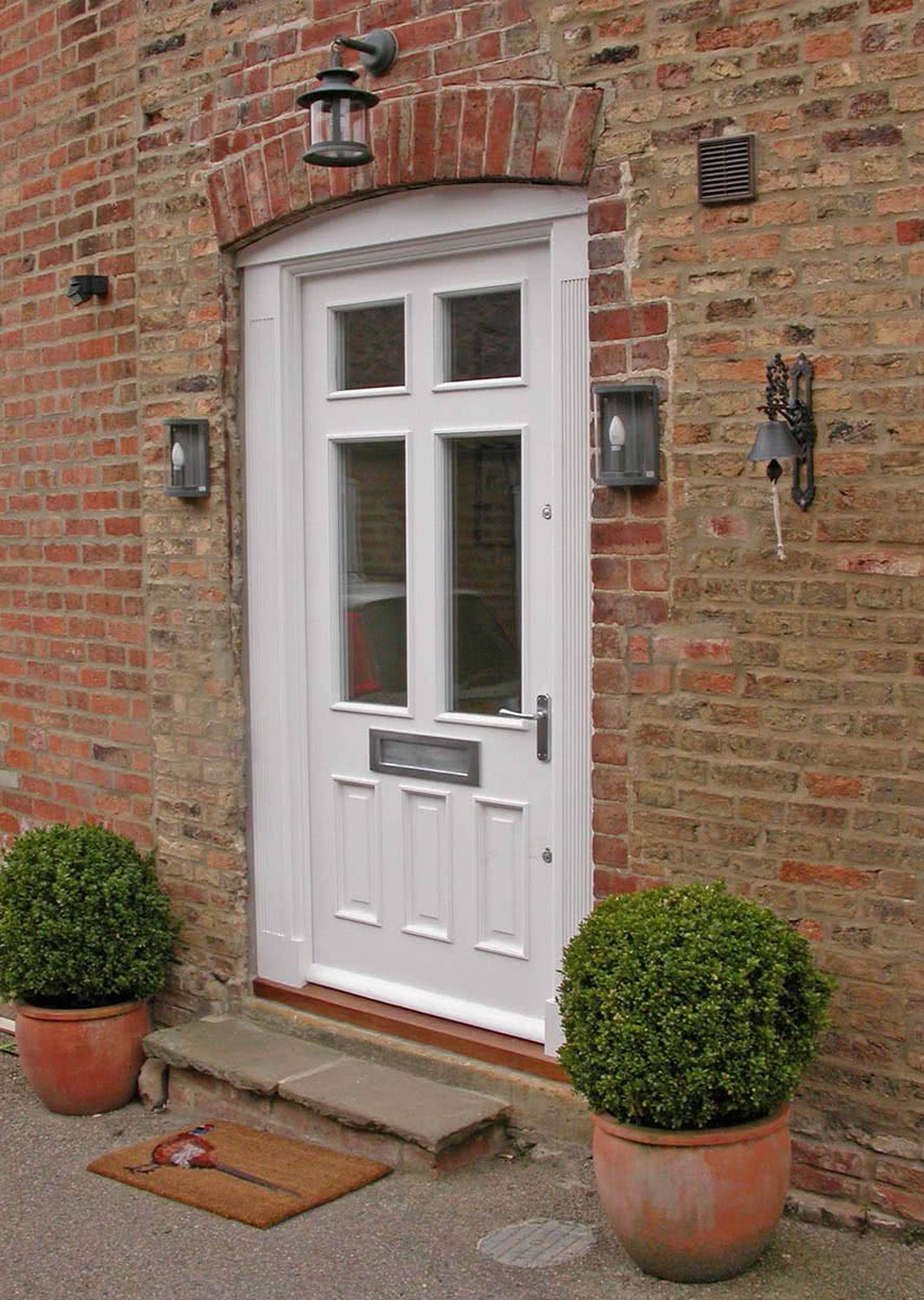 Exterior view of fitted meranti hardwood door with four double glazed windows and with three raised panels