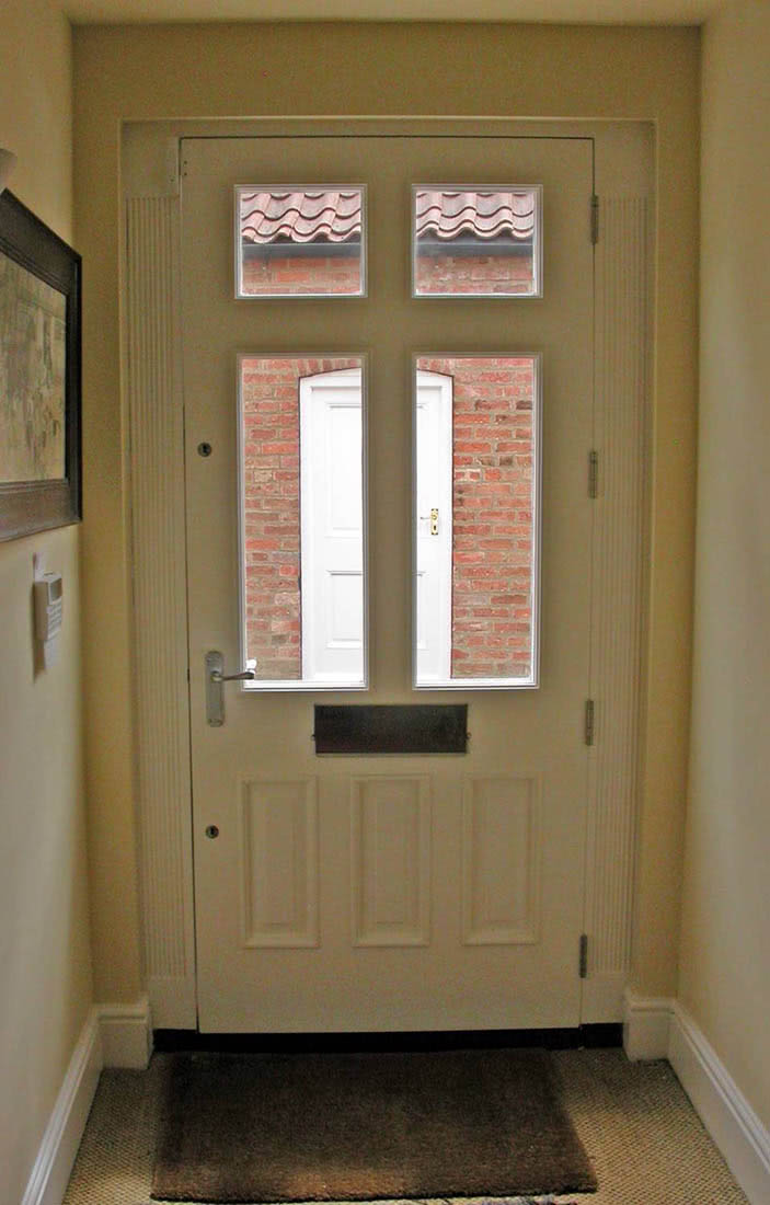 Interior view of handmade meranti hardwood door with four double glazed windows and with three raised panels