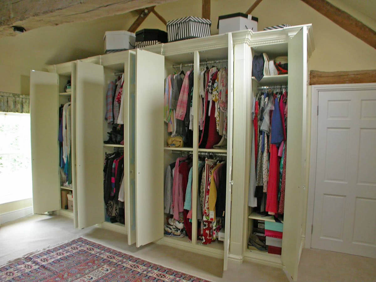 Large fitted country style wardrobes with doors open showing shelving and clothes rails