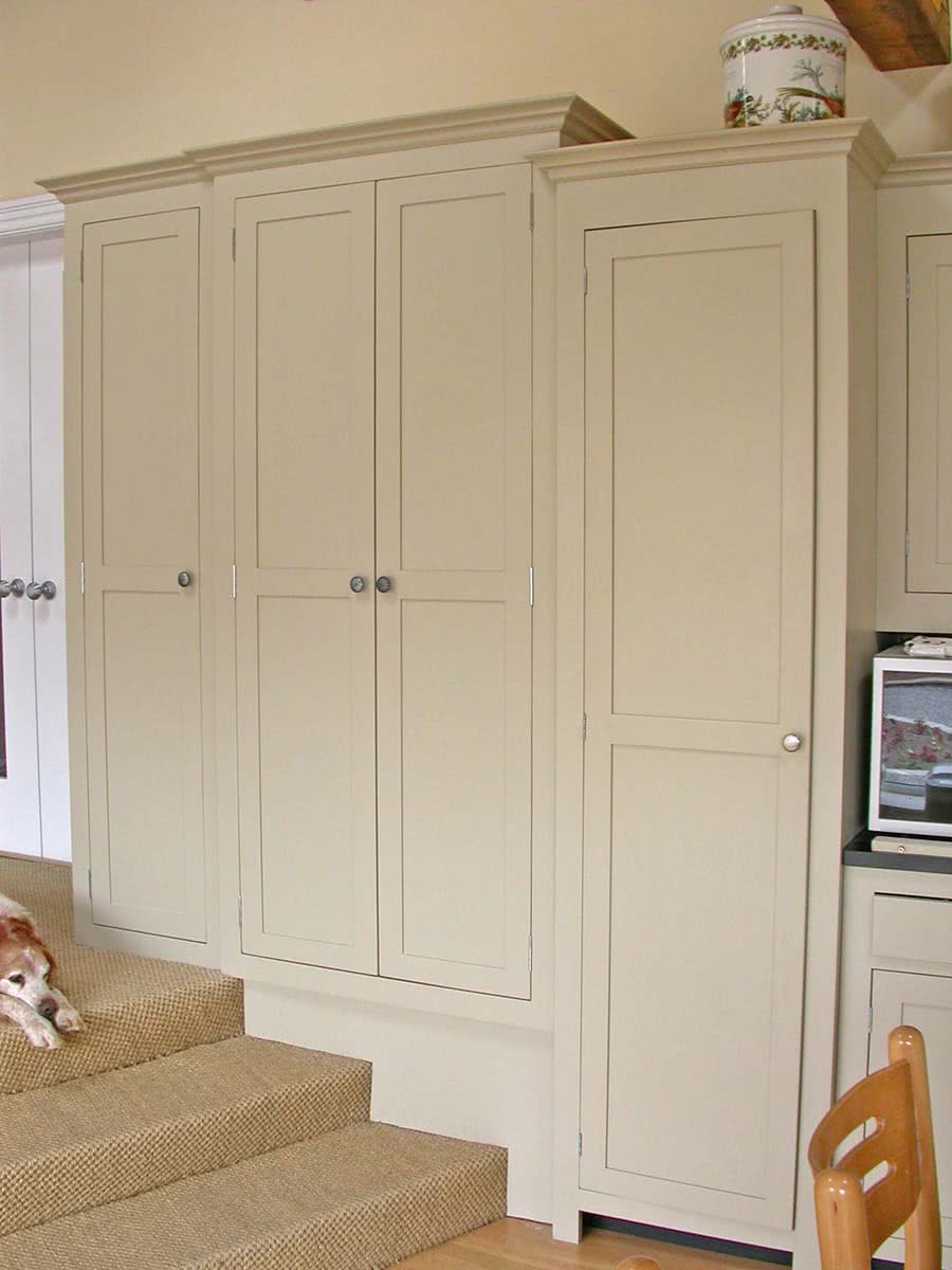 One kitchen cabinet full height with single door and one cabinet double door also full height in cream colour fitted snugly over steps