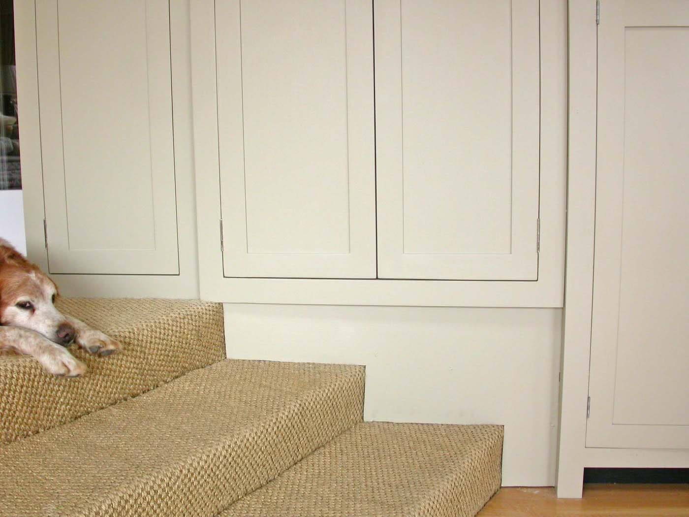 Close up of new kitchen cabinets fitted snugly over steps, with dog on top of steps