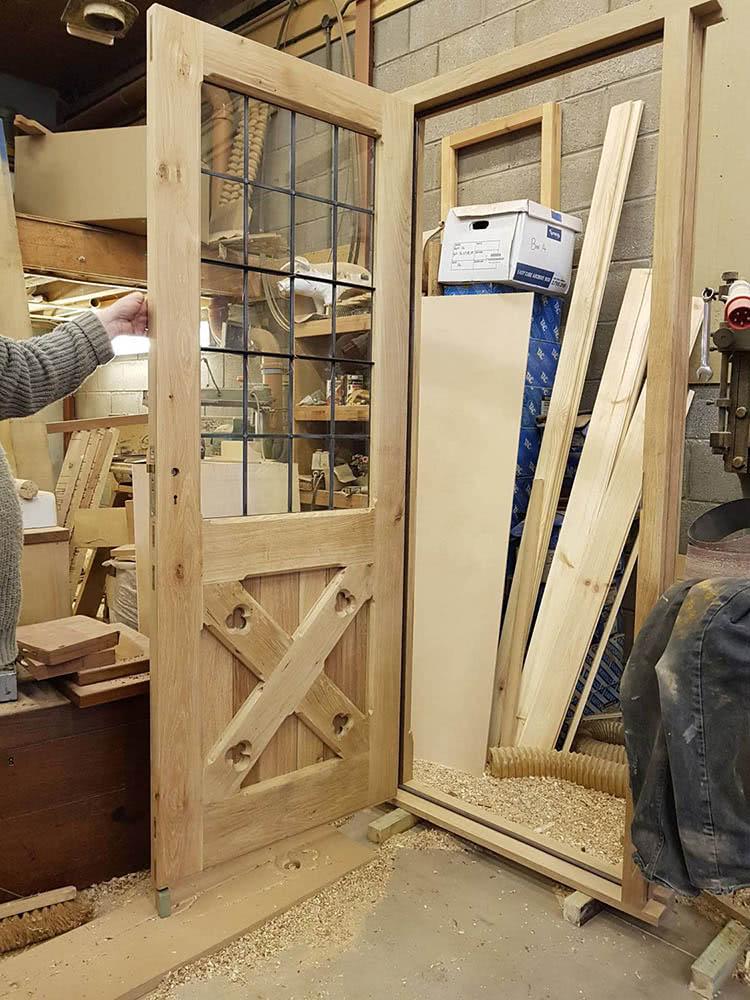 Oak door with leaded glass panes open from frame in workshop