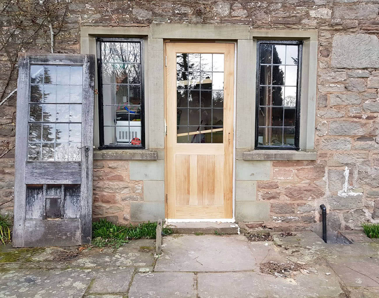 Newly fitted bespoke oak door with leaded glass panes side by side comparison with the old door