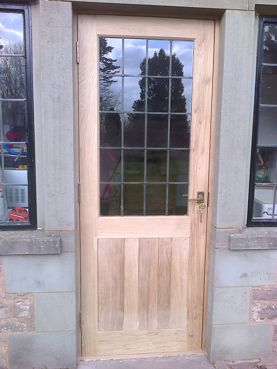 Close up of fitted oak door with leaded glass panes with antique handle