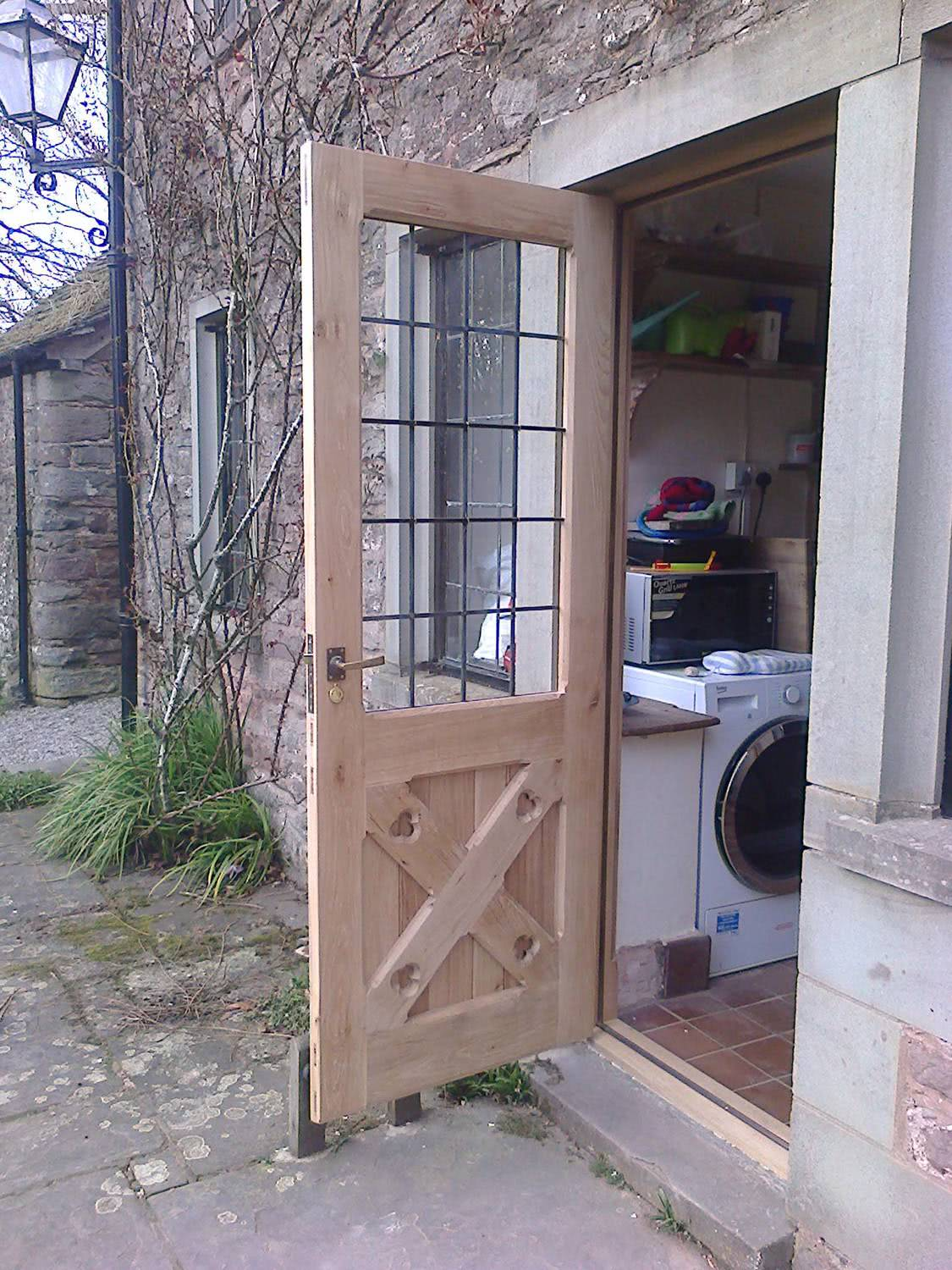 Open oak door with leaded glass panes fitted on customer property