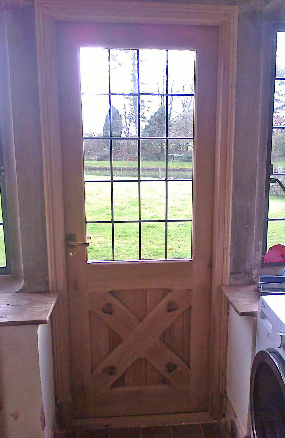 Closed interior shot of newly fitted oak door with leaded glass panes