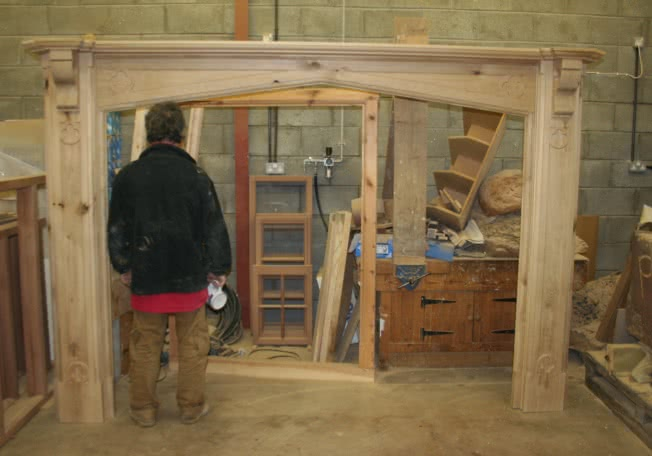 Large oak fireplace in workshop. Man standing next to pillar for size