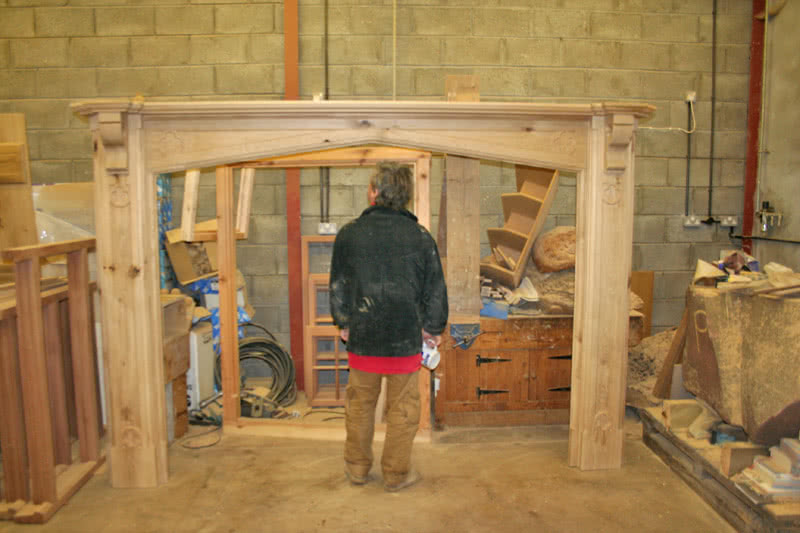 Large oak fireplace in workshop. Man standing in centre of opening for size