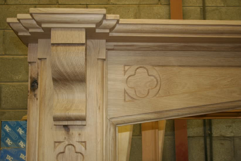 Large oak fireplace in workshop. Decorative quatrefoil carved into corbel