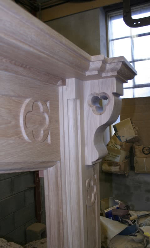 Large oak fireplace in workshop. Right hand side pillar with relief quatrefoil set in mantelpiece and decorative quatrefoil carved into corbel
