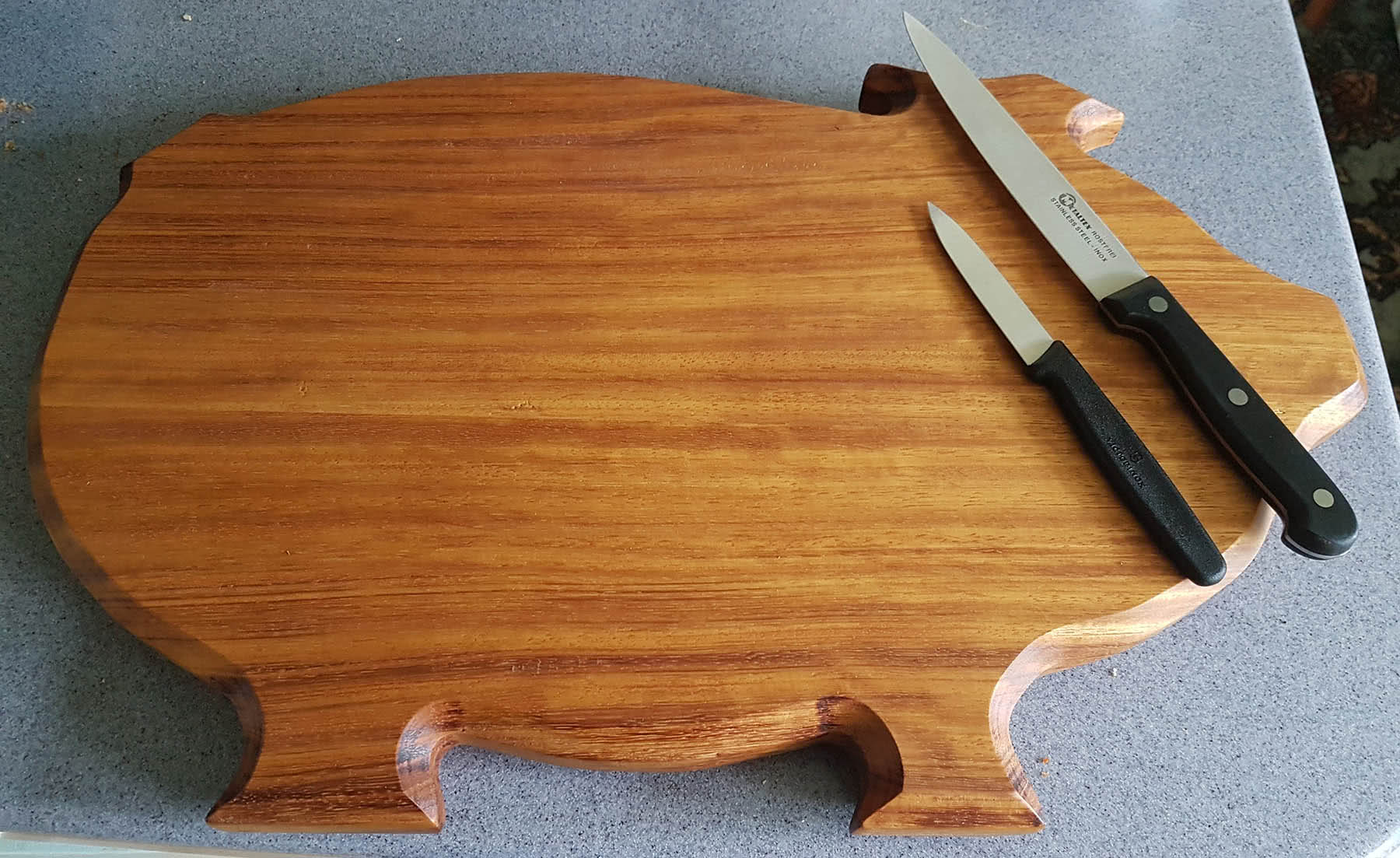 Pig shaped chopping board in Iroko wood with top knives near snout