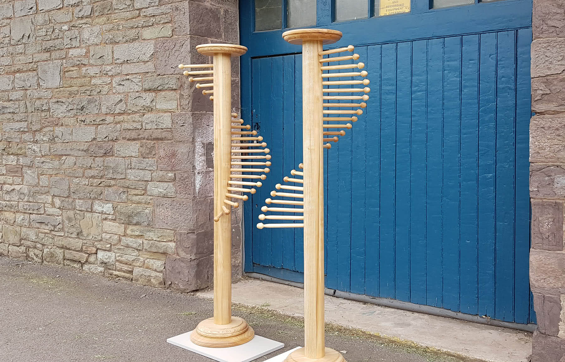 Pair of handmade belt/scarf stands outside of workshop