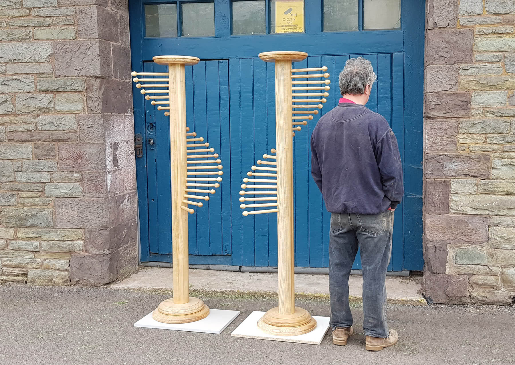 Pair of handmade belt/scarf stands outside of workshop with man standing near for size comparison